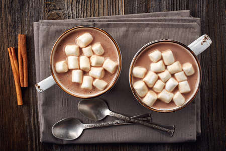 Photo for Two cups of hot cocoa with marshmallows and cinnamon sticks on wooden background - Royalty Free Image