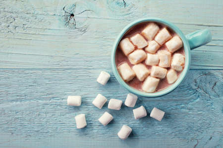 Photo for Blue cup of hot cocoa with marshmallows on blue wooden background - Royalty Free Image