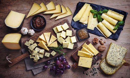 Photo pour Cheese plates served with grapes, jam, figs, crackers and nuts on a wooden background, Top view - image libre de droit