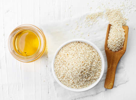 Foto de Sesame seed oil and bowl of sesame seeds on white wooden background. Top view - Imagen libre de derechos