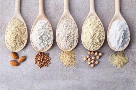 Photo pour Wooden spoons of various gluten free flour (almond flour, amaranth seeds flour, buckwheat flour, rice flour, chick peas flour) from top view - image libre de droit