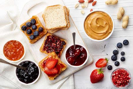 Foto de Sandwiches with peanut butter, jam and fresh fruits on white wooden background from top view - Imagen libre de derechos