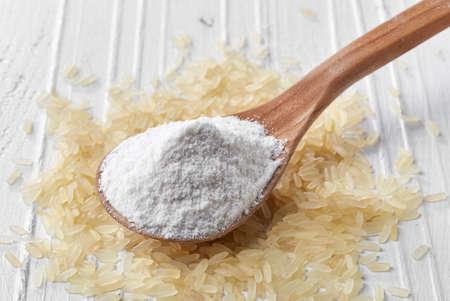 Foto de Spoon of rice flour on white wooden background - Imagen libre de derechos
