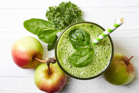 Photo pour Glass of green fruit and vegetable smoothie on white wooden background from top view - image libre de droit