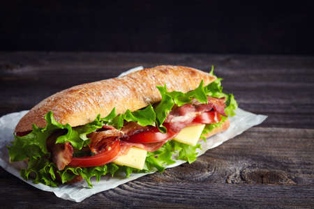 Photo for Fresh submarine sandwich with ham, cheese, bacon, tomatoes, cucumbers, lettuce and onions on dark wooden background - Royalty Free Image