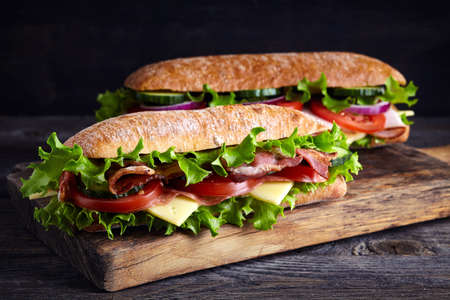 Photo pour Two fresh submarine sandwiches with ham, cheese, bacon, tomatoes, lettuce, cucumbers and onions on wooden cutting board - image libre de droit