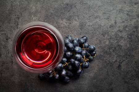Photo pour Glass of red wine and grapes on dark gray background from top view - image libre de droit
