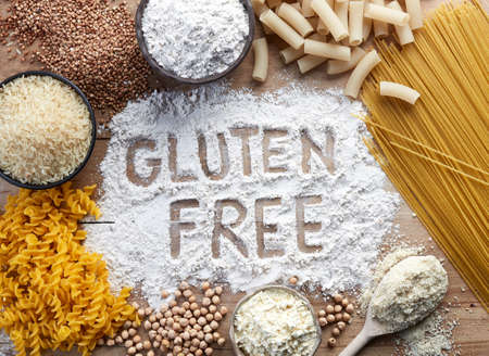 Foto de Gluten free food. Various pasta and flour (rice, buckwheat, corn, chickpeas) on wooden background from top view. - Imagen libre de derechos