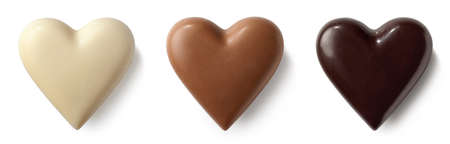 Foto de Three chocolate (milk, dark and white) hearts isolated on white background. Top view - Imagen libre de derechos