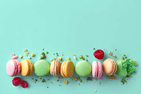 Photo pour Row of colorful french macarons on blue background. Top view. Pastel colors - image libre de droit