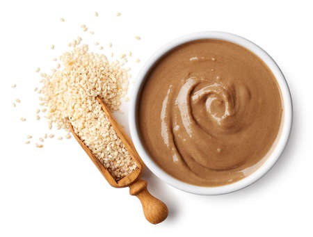 Foto de Bowl of tahini sauce and sesame seeds isolated on white background. Top view - Imagen libre de derechos
