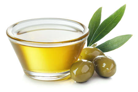 Foto de Glass bowl of fresh extra virgin olive oil and green olives with leaves isolated on white background - Imagen libre de derechos