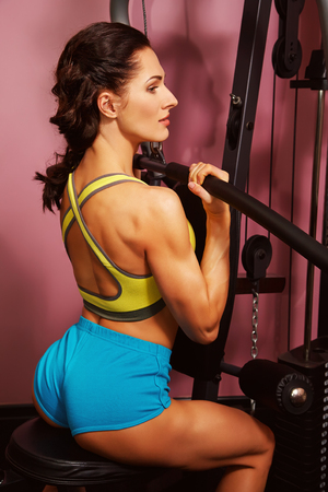 Foto per woman doing exercises on training apparatus in gym - Immagine Royalty Free