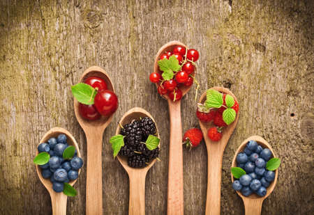 Photo for Berries in wooden spoons on wood texture - Royalty Free Image