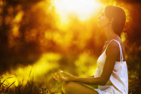 Photo pour Yoga woman meditating at sunset. Female model meditating in serene harmony - image libre de droit