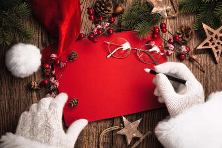 Foto de Santa Claus with gifts and red card on wooden table - Imagen libre de derechos