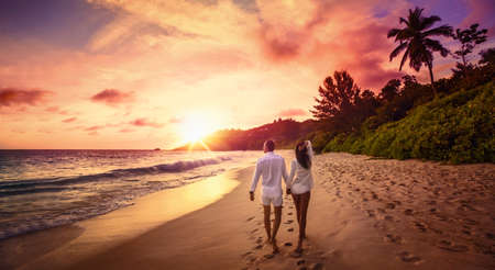 Photo pour Young Happy Lovers on Beach. Couple Walking on Romantic Travel Honeymoon Vacation Summe Holidays Romance Sunset - image libre de droit