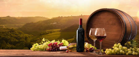 Photo pour Bottles And Wineglasses With Grapes And Barrel On A Sunny Background. Italy Tuscany - image libre de droit