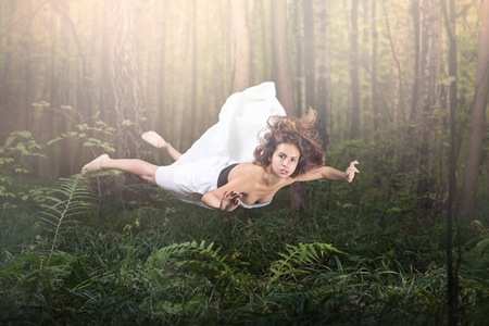 Foto de Zero gravity. Young beautiful woman flying in a dream. Forest green and glow. White dress and hair in the air. Surprise and light fright - Imagen libre de derechos