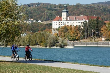 Foto de YBBS AN DER DONAU, AUSTRIA - OCTOBER 14, 2018. Middle-aged couple riding bicycles along the Danube river on the famous cycling route Donauradweg. View of the Persenbeug castle. Lower Austria, Europe. - Imagen libre de derechos