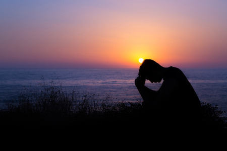 Photo pour Young man praying to God during sunset by the sea - image libre de droit