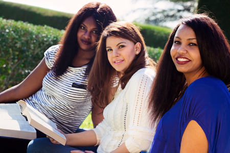 Three Christian girls studying the Bible and looking at the camera
