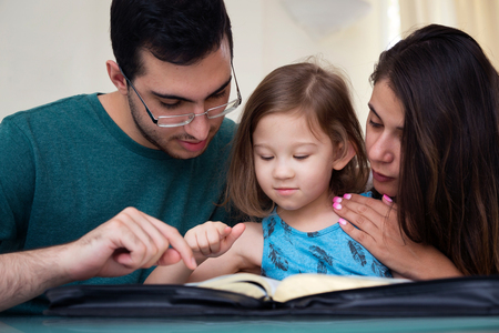 Photo pour Young family studying the Word of God - image libre de droit