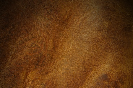 Distressed brown leather texture background lit from above