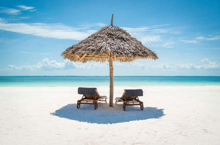 Foto de 2 wooden sun loungers facing the tropical, turquoise blue Indian Ocean under a thatched umbrella on a white sandy Zanzibar beach - Imagen libre de derechos