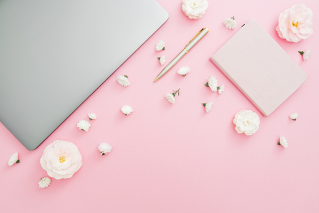 Photo for Stylish office desk workspace with laptop, notebook, pen and flowers on pink background. Top view. Flat lay lifestyle concept. - Royalty Free Image