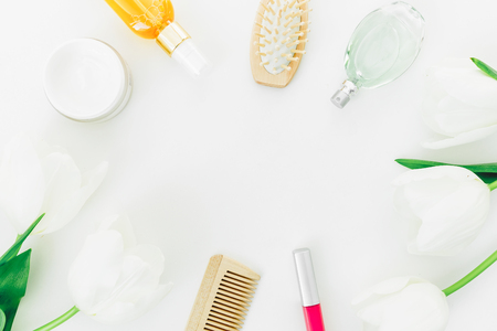 Photo pour Frame with perfume, cosmetics, combs and tulips flowers on white background. Beauty blogger composition. Flat lay, top view - image libre de droit