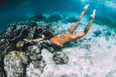 Foto de Beautiful naked woman swimming and dive in tropical ocean. Underwater photo with woman near coral reef - Imagen libre de derechos