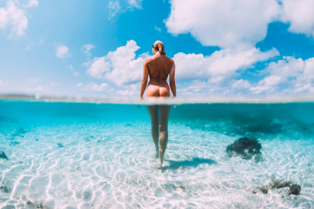 Photo pour Beautiful naked woman in tropical ocean, underwater fifty fifty photo. Bahamas island - image libre de droit