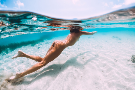 Photo pour Attractive naked woman swimming in tropical blue ocean, underwater - image libre de droit
