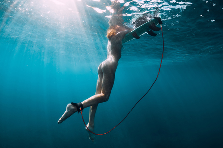 Foto de Naked surfer woman in sea. Nude young woman with surfboard, underwater - Imagen libre de derechos