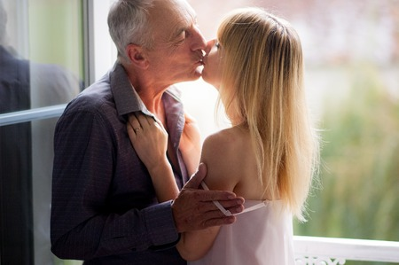 Photo pour Portrait of Attractive Young Woman Kissing Her Senior Husband near Opened Windows in the Room During Summer Time. Age Difference Concept. - image libre de droit
