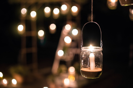 Foto de The lamp made of a jar with a candle  is  hanging  on a tree at night. Wedding night decor. Night ceremony - Imagen libre de derechos