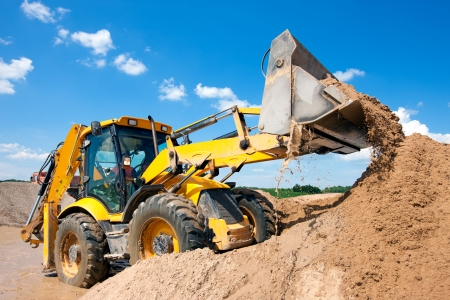 Photo for Excavator machine unloading sand with water during earth moving works at construction site - Royalty Free Image