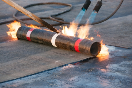 Photo pour Roll roofing Installation with propane blowtorch - image libre de droit