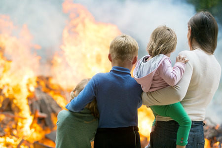 Photo for Family of mother with children at burning house background - Royalty Free Image
