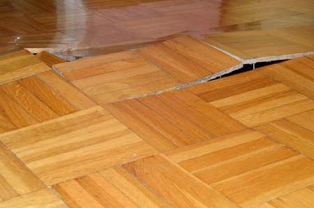 Foto de Damage of wooden floor. Parquet lifted up under influence of destructive elements. - Imagen libre de derechos