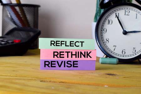 Foto de Reflect Rethink Revise. Handwriting on sticky notes in clothes pegs on wooden office desk - Imagen libre de derechos