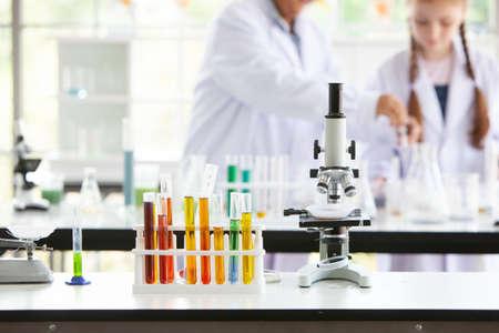 Foto de Test tubes and microscope on a table in the laboratory - Imagen libre de derechos