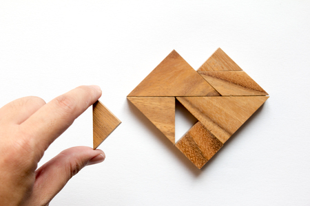 Foto de Man held piece of tangram puzzle to fulfill the heart shape on white background (Concept of love) - Imagen libre de derechos