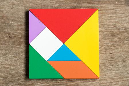 Foto de Colorful tangram puzzle in square shape on wood background - Imagen libre de derechos