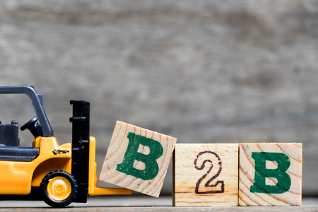 Foto per Yellow plastic forklift hold letter B to complete word B2B (Business to business) on wood background - Immagine Royalty Free