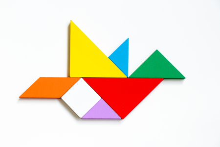 Photo pour Colorful wood tangram puzzle in flying bird shape on white background - image libre de droit
