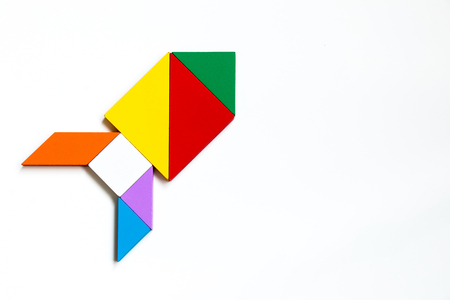 Foto de Colorful wood tangram puzzle in rocket or missile shape on white background - Imagen libre de derechos