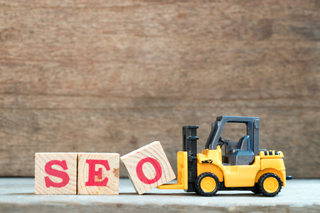 Photo for Yellow toy forklift hold letter block O to complete word SEO (Abbreviation of search engine optimization) on wood background - Royalty Free Image