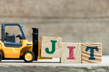Foto de Toy yellow forklift hold letter block J to complete word JIT (Abbreviation of Just in time)on wood background - Imagen libre de derechos